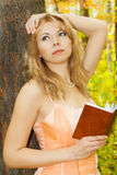 Beautiful woman with book near tree. In forest. Sun day Stock Images