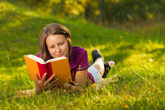 Beautiful woman with a book in the park Stock Images
