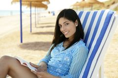 Beautiful woman with a book relaxed on the beach Stock Image