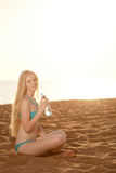 Beautiful woman with a bottle of water on the beach Stock Image