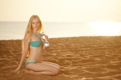 Beautiful woman with a bottle of water on the beach Royalty Free Stock Images