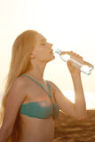 Beautiful woman with a bottle of water on the beach Royalty Free Stock Photo