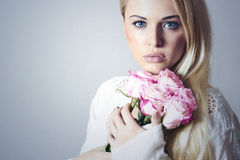 Beautiful Woman with bouquet of Flowers.Blond girl.roses Royalty Free Stock Photo