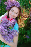 Beautiful woman with a bouquet of flowers walking in the spring park Stock Image