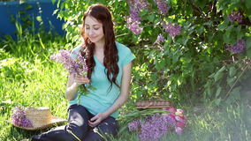 Beautiful woman with a bouquet of lilac sitting in the spring park on the grass.  stock video footage