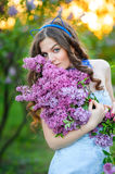 Beautiful woman with a bouquet of lilacs in the spring Stock Photography