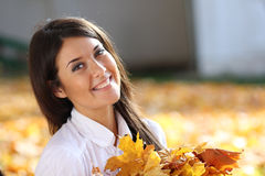 Beautiful woman with a bouquet of maple leaves Stock Image