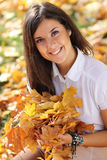 Beautiful woman with a bouquet of maple leaves Stock Images