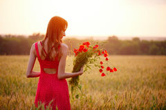 Beautiful woman with bouquet of poppies in a wheat field Royalty Free Stock Photos