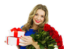Beautiful woman with bouquet of red roses and gift boxes Stock Image