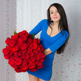 Beautiful woman with a bouquet of red roses Stock Photography