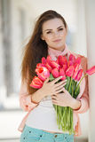 Beautiful woman with a bouquet of red tulips Stock Photography