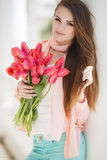 Beautiful woman with a bouquet of red tulips Royalty Free Stock Photography