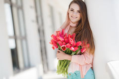 Beautiful woman with a bouquet of red tulips Royalty Free Stock Images