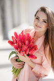 Beautiful woman with a bouquet of red tulips Stock Images