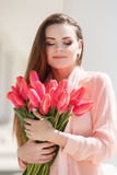 Beautiful woman with a bouquet of red tulips Royalty Free Stock Image