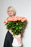 Beautiful woman with a bouquet of roses. On a white background Stock Image