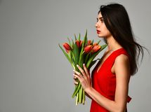Beautiful woman with bouquet of tulip flowers in red dress and little sticker on tulips Stock Photography
