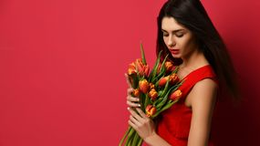 Beautiful woman with bouquet of tulip flowers in red dress and looking at the corner with empty text copy space Stock Photos