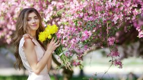 Beautiful woman with bouquet of tulips at flowered garden stock footage