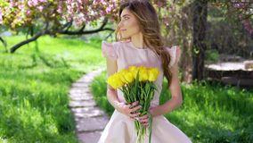 Beautiful woman with bouquet of tulips at flowered garden stock video footage