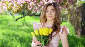 Beautiful woman with bouquet of tulips at flowering garden stock video footage