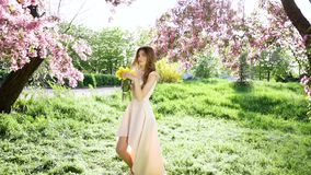 Beautiful woman with bouquet of tulips at flowering garden stock video