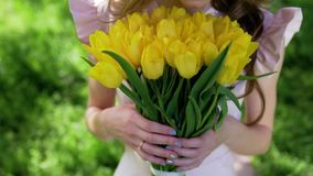Beautiful woman with bouquet of tulips at flowering garden. Attractive woman at spring concept. Medium shot. Petals falls from trees stock footage