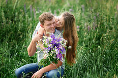 Beautiful woman with bouquet of wild flowers hugging man sitting on the grass in meadow Stock Photos