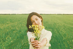 Beautiful woman with a bouquet of yellow flowers Stock Image