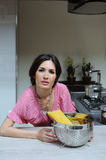 Beautiful woman with a bowl of pasta cooking dinner in the kitchen Royalty Free Stock Image