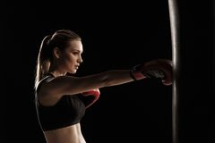 Beautiful woman is boxing on black background Stock Images