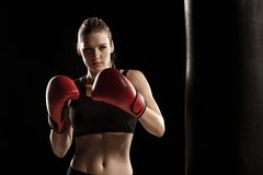 Beautiful woman is boxing on black background. Beautiful woman with the red gloves is boxing on black background Royalty Free Stock Images