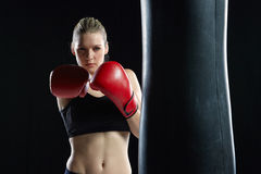 Beautiful woman is boxing on black background Royalty Free Stock Images