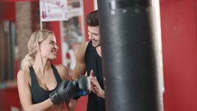 Beautiful woman boxing combat bag with sport trainer together. stock video footage