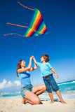 Beautiful woman and boy holding arms with kite Royalty Free Stock Photography