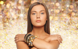 Beautiful woman with bracelets over golden lights Stock Photo
