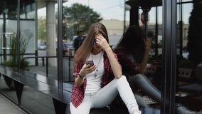 Beautiful woman in branded glasses and casual clothes using her phone near shopwindow stock footage