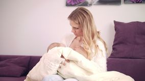 Beautiful woman breast feeding baby at home. Little baby care