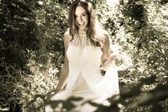 Beautiful woman, bride with blue eyes and brown hair walks through leafy woods, woodland on a bright sunny summer`s day. Beautiful woman, bride with white dress royalty free stock image