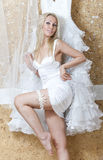 Beautiful woman, the bride,  with a garter on a foot near a wedding dress Stock Photo