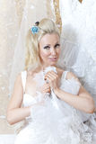 Beautiful woman, the bride,  with a garter on a foot near a wedding dress Stock Photography