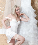 The beautiful woman, the bride, in with a garter on a foot near a wedding dress.portrait to the utmost Stock Photography