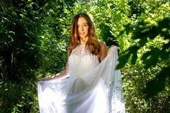 Beautiful woman, bride with blue eyes and brown hair walks through leafy woods, woodland on a bright sunny summer`s day. Beautiful woman, bride with white dress stock images