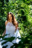 Beautiful woman, bride with blue eyes and brown hair walks through leafy woods, woodland on a bright sunny summer`s day. Beautiful woman, bride with white dress royalty free stock photos