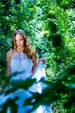Beautiful woman, bride with blue eyes and brown hair walks through leafy woods, woodland on a bright sunny summer`s day Royalty Free Stock Photos