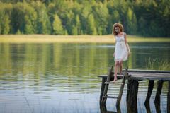 Beautiful woman on bridge on Lake Stock Photography