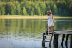 Beautiful woman on bridge on Lake Stock Images