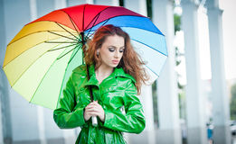 Beautiful woman in bright green coat posing in the rain holding a multicolored umbrella Royalty Free Stock Photography