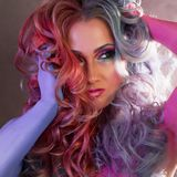 Beautiful woman with bright hair. Body painting and bright hair coloring. Beautiful woman with bright hair. Bright hair color, hairstyle with the curls Royalty Free Stock Photos